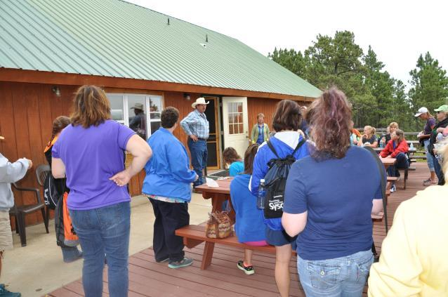 John Hanson welcomes the teachers to the Logging Camp Ranch near the edge of the ponderosa pine forest.