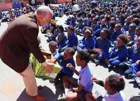 Not even the Cape Doctor could dampen the children s enthusiastic smiles when they each received a red apple.