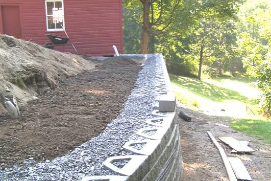 When compacting over the geogrid, work from near the retaining wall units toward the tail of the geogrid. This procedure helps keep the geogrid taught.