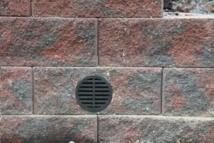 The drain pipe is placed in the leveling pad directly under the drainage aggregate chimney.