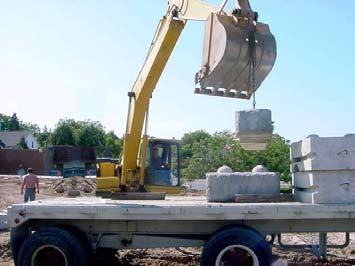 SETTING THE BOTTOM ROW OF WALL BLOCKS... Redi-Rock blocks are typically delivered to the construction site using a flat bed trailer or boom truck.