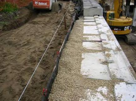 Generally, the drain tile runs along the back of the wall and is located near the bottom of the drainage aggregate zone.