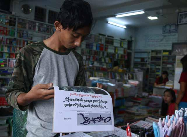 A reader picking up Tanintharyi Weekly at a bookstore in Dawei. including reader surveys, and the development of markets in other towns.